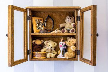 Öppet skåp i trä med gamla minnen och saker.