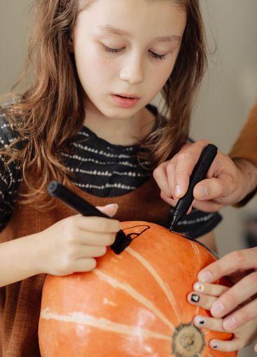 little girl paints a pumpkin for Halloween. preparation...