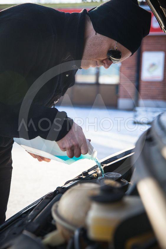 Man fyller på spolarvätska i bil under vinter
