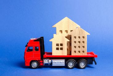Red truck transports wooden houses. Concept of...