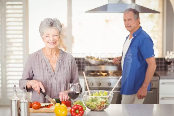 Happy senior woman cutting vegetables with husband in...