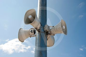 four megaphone hanging on a pole