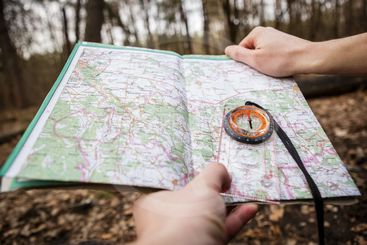 man holding compass and map in the forest