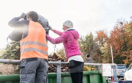 Woman and man giving waste green in container on...