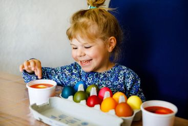 Excited little toddler girl coloring eggs for Easter....