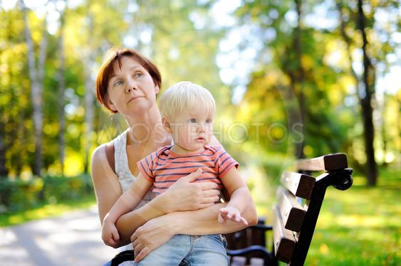 Woman and her toddler grandson enjoy sunny autumn day