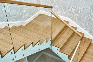 Wooden staircase with glass railings and wooden handrail
