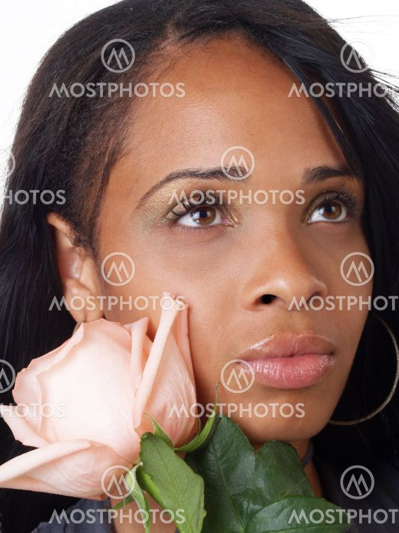 Young black woman with pink rose along cheek