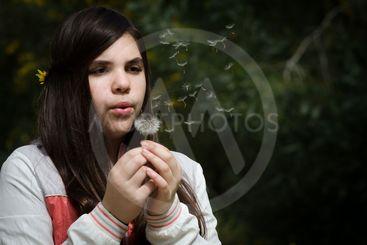 Young beautiful Girl blowing dandelion flower