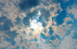 Stormy white clouds on blue sky and sun behind clouds