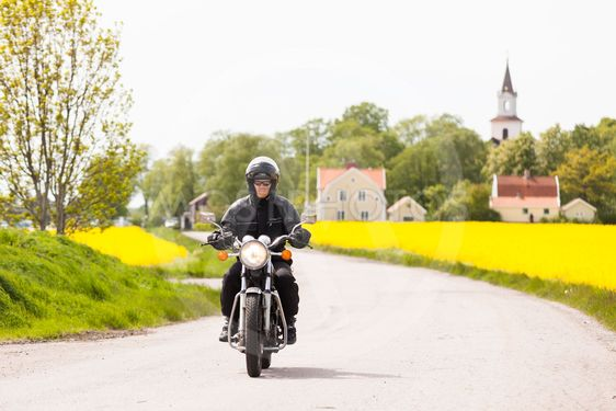 Man kör motorcykel på landsväg vid rapsfält