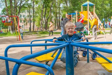 A three-year-old blond boy in a leisure park rides on a...