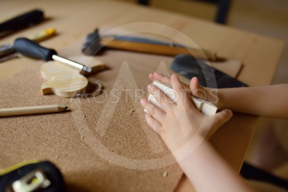 Little boy learns work with tools. Kid make a wooden toy....