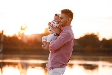 dad hugging his little daughter near the lake on sunset....
