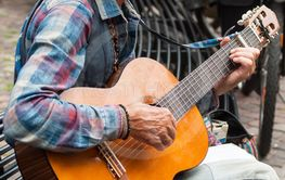Portrait of old man playing acoustic guitar in the street