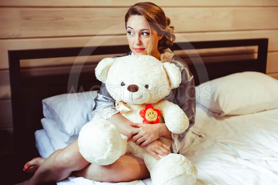 girl sitting on bed with soft toy