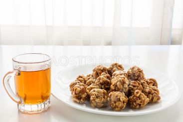 Sweet peanut balls in a plate and glass of black tea