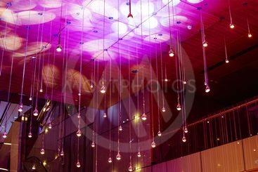Many round lamps under ceiling. Glowing lamps in dark...