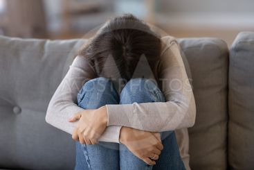 Depressed woman sitting on couch feeling unhappy crying...