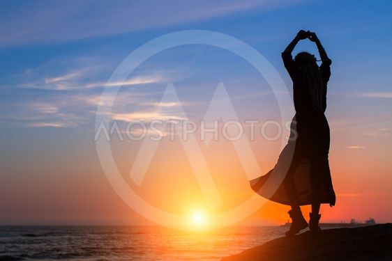Silhouette of dancing woman on the sea coast during...