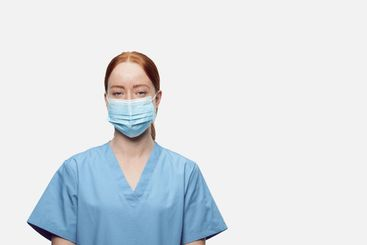 Young nurse with masks looking at camera