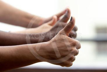 Close up of multiethnic people show thumbs up gesture