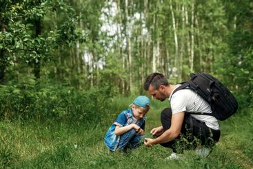 A man with a backpack, a father and his son on a hike,...