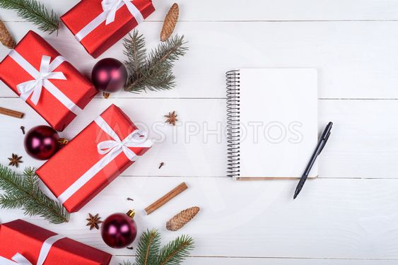 Top view of blank notebook on white wooden background with xmas decorations, copy space. Christmas background with notebook for wish list or to do list, ...