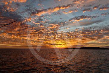 Vibrant Orange colored cloudy sunset seascape. Coastal...