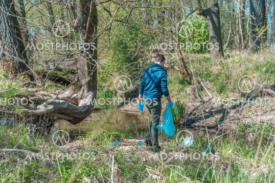 volunteer collects plastic waste in nature, cleaning in...