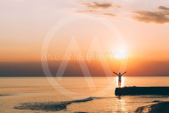 Young woman standing with raised arms in sunset