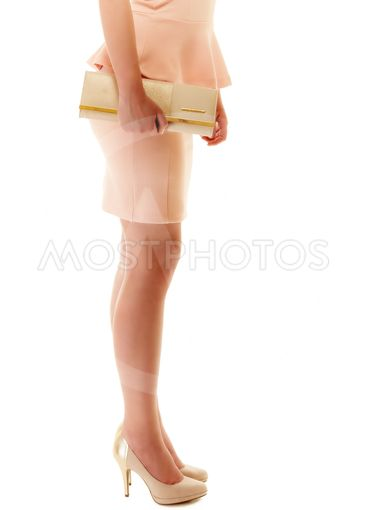 Handbag and legs of girl in pink dress and high heels