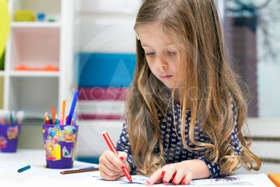Little girl drawing at playroom
