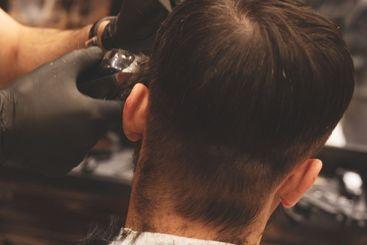 Haircut head in barbershop. Barber cuts the hair on head...