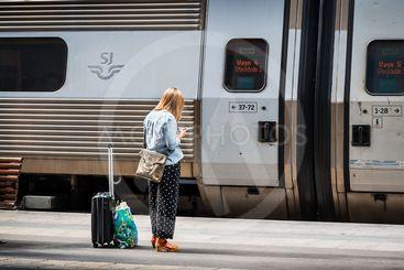 Ut i världen: Väntande resenär med resväska vid ett tåg