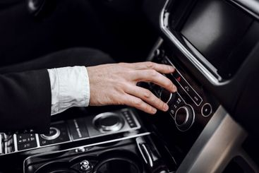 Businessman changing radio station while driving automobile