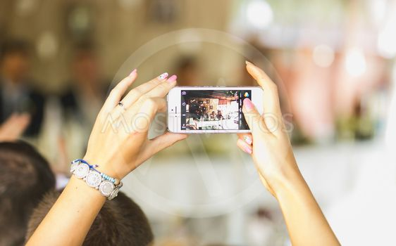 woman making photo on mobile phone at wedding ceremony