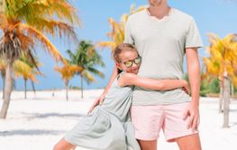 Father and little girls have a lot of fun on white sandy...