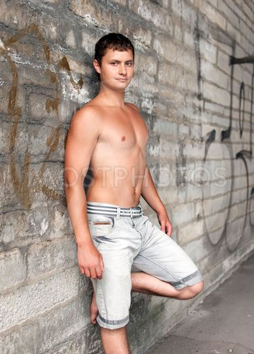 muscular guy standing near the wall on the street