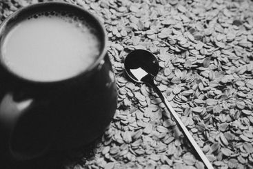 A metallic spoon over of a bunch of oat seeds with a cup...