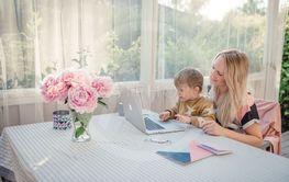 Mamma och son sitter vid dator ute på altanen en...
