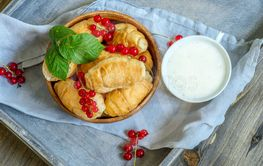 Croissants with currant berries on a wooden tray. The...