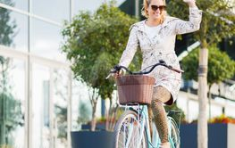 Young happy woman riding a bicycle in the city