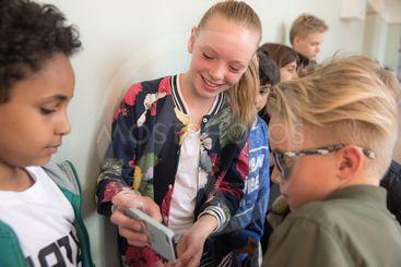 barngrupp tittar på mobiltelefon under rast