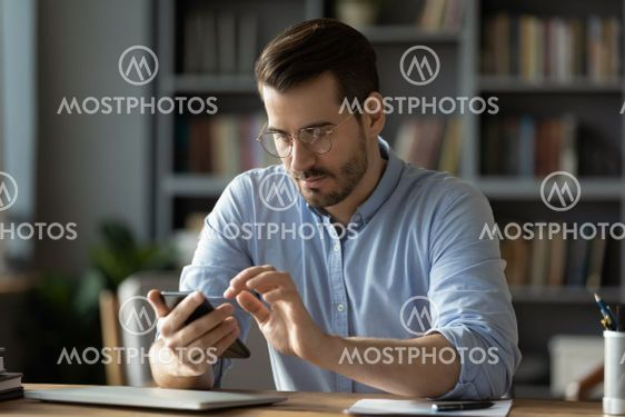 Serious businessman wearing spectacles using mobile...
