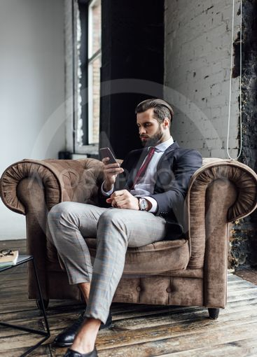 confident businessman texting sms on smartphone while...