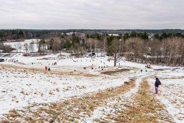 Skidbacke i Järfälla med gräs och första snön.