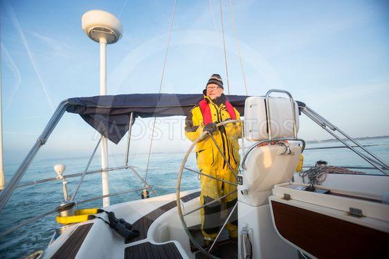 Man Steering Wheel Of Sail Boat In Sea