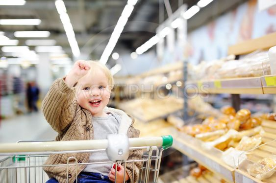 Toddler boy sitting in the shopping cart in a supermarket