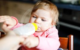 Cute adorable baby girl holding nursing bottle and...
